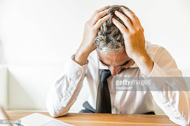 Overstressed businessman with head in his hands