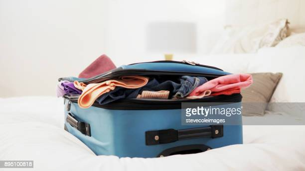 overstuffed suitcase on top of bed. - packing stock pictures, royalty-free photos & images