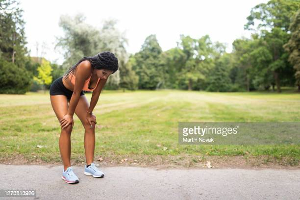 overtraining by young woman athlete taking a break - tired stock pictures, royalty-free photos & images