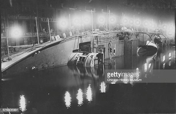 Overturned Eastland ship in the Chicago River at night, Chicago, Illinois, 1915. Powerful electric lights aid workers and rescuers.