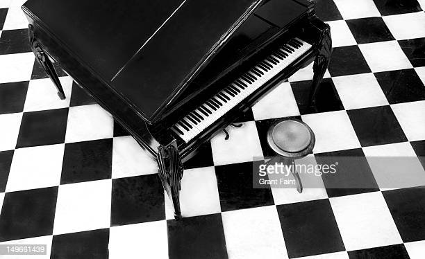 overview of a grand piano on a checkered floor - grand piano stock photos and pictures