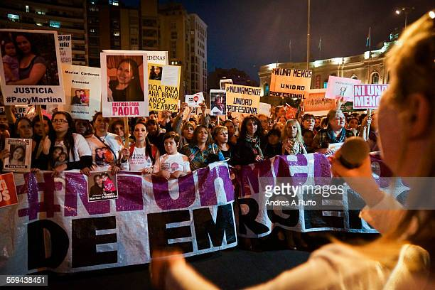 Overview of a large group of people marching to demand urgent measures against gender violence and femicide tellsufficient under the banner and...