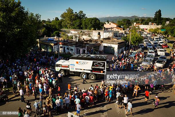 Overview of a large group of people waiting for the arrival of the official car of the Dakar 2015 on a street entrance to property located in the...