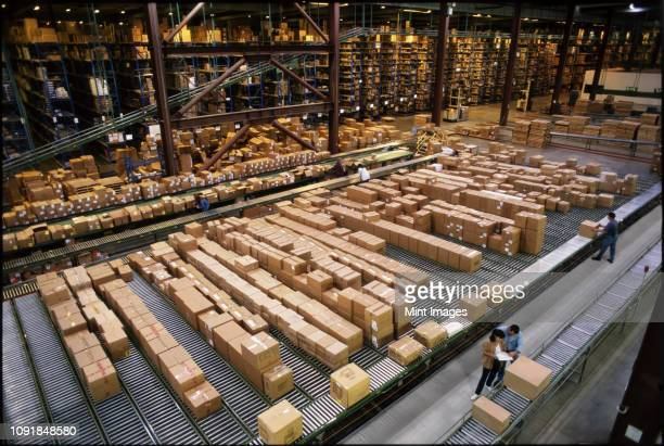 overview of a large industrial distribution warehouse storing products in cardboard boxes on conveyor belts and racks. - industry stock pictures, royalty-free photos & images