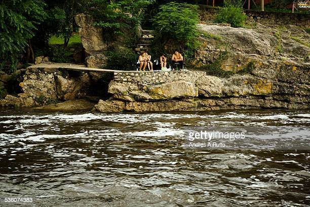 Overview of a small group of people sitting on a rock watching the river mega flood with water in the spa El Fantasio located in the city of Villa...