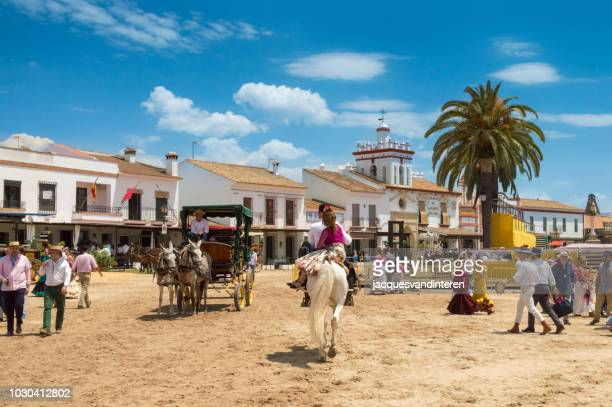 overview of one of the streets of el rocio during the romeria del rocio (pilgrimage), spain. - donana national park stock photos and pictures