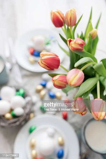 overview of the easter breakfast table with chocolate eggs and flowers. - easter flowers stock pictures, royalty-free photos & images
