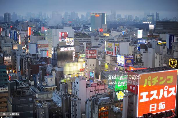 CONTENT] Overview of the neonlit buildings of Tokyo's Shinjuku business district on a rainy evening in January 2009 A sign for a pachinko parlor is...