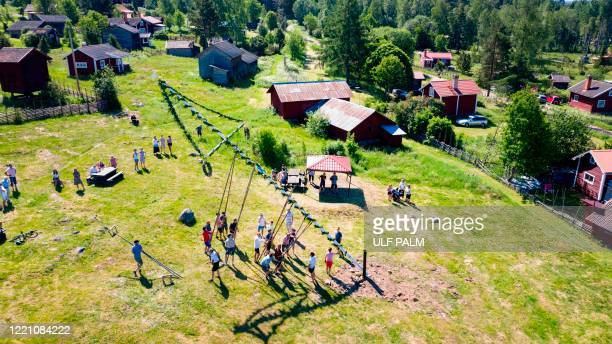 Overview taken on June 19 2020 shows people erecting a maypole for midsummer celebrations in Sahl near Leksand Sweden In the small village of Sahl in...