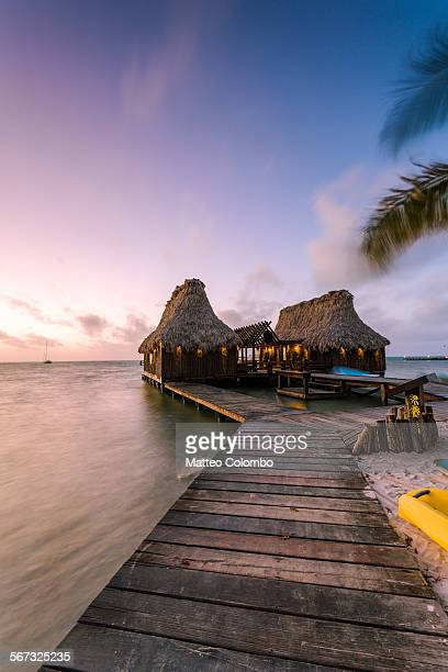 Overwater bungalow and jetty at sunset, Belize