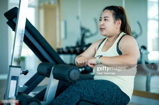 overweight asian woman doing sit ups by sit-up machine at gym. - body positive stock pictures, royalty-free photos & images