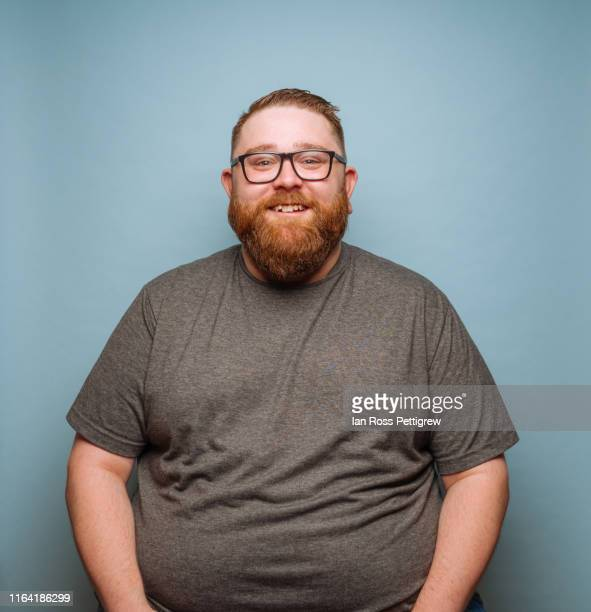 overweight bearded hipster on blue background - beard stock pictures, royalty-free photos & images