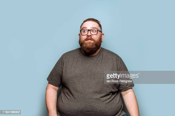 overweight bearded hipster on blue background - gordo fotografías e imágenes de stock
