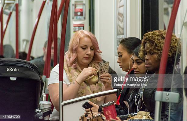 Overweight blonde woman using smartphone inside train sitting near three women of different races who are listening to music on their mobile devices