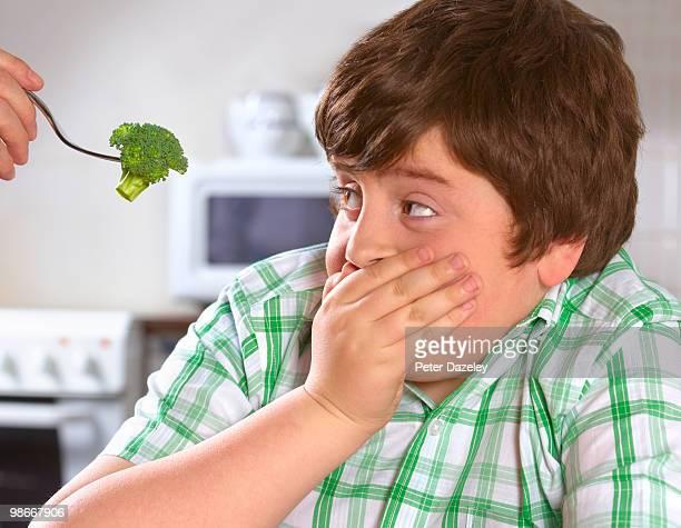 Overweight boy hates broccoli