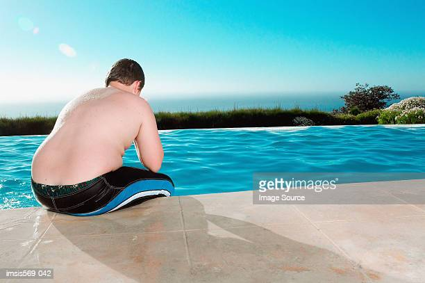 overweight boy having a break from swimming - fat kid stock photos and pictures