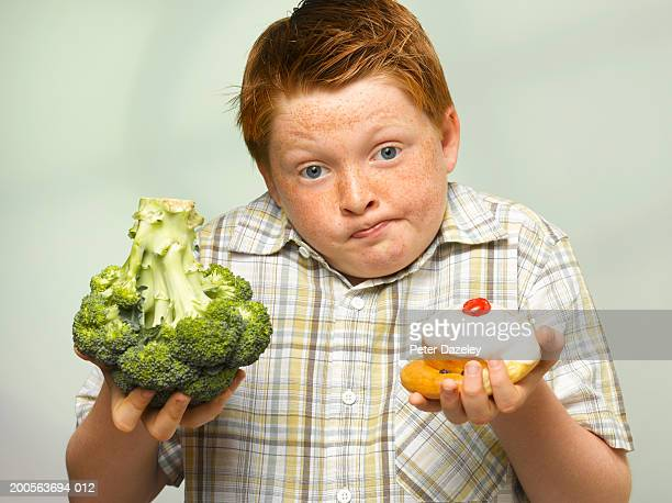 Overweight boy (10-11) holding up head of broccoli and cake, portrait