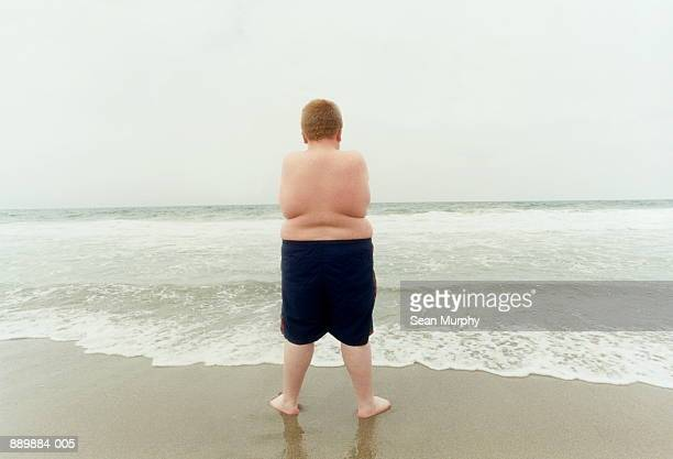Overweight boy (10-12) standing on beach, rear view