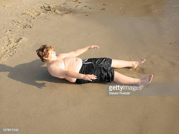 Overweight boy trying to get up at the beach