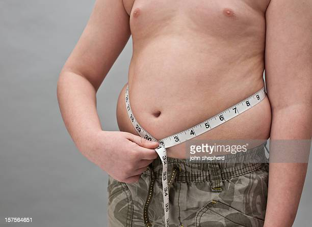 Overweight Boy with tape measure around belly
