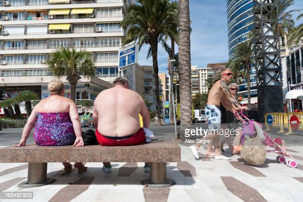 CONTENT] Overweight British holidaymakers sunbathing on the waterfront in Benidorm Costa Blanca Spain