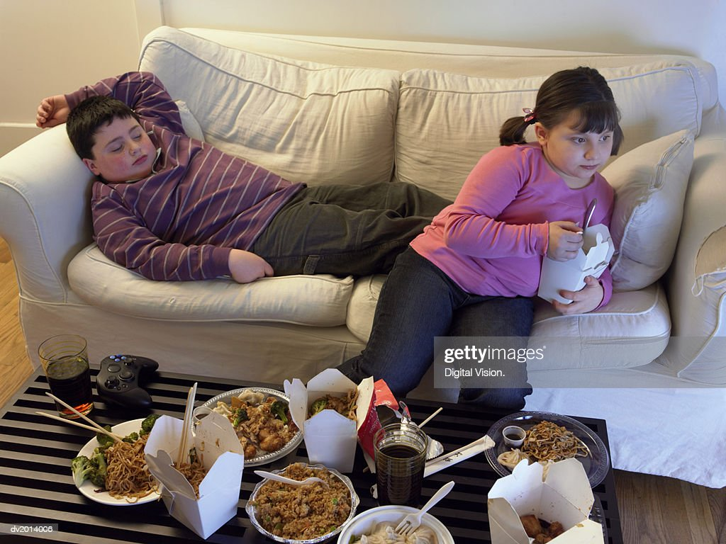 Overweight Brother and Sister on a Sofa Eating Takeaway Food and Watching the TV : Stock Photo