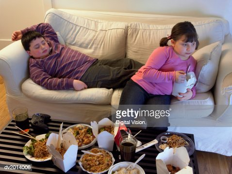 Overweight Brother And Sister On A Sofa