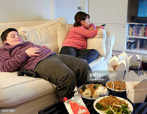 overweight brother and sister sitting on a sofa eating takeaway food and watching the tv - chubby boy stock photos and pictures