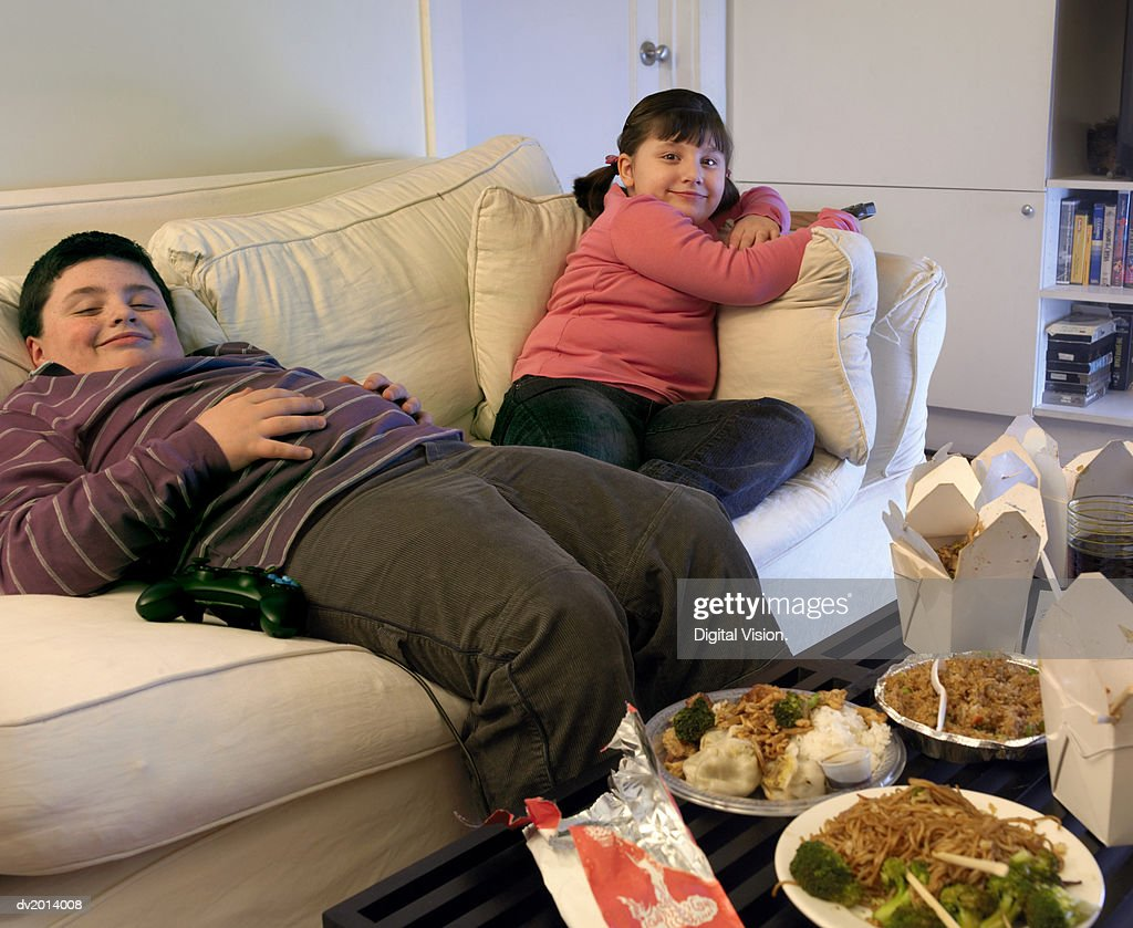 Overweight Brother and Sister Sitting on a Sofa Eating Takeaway Food and Watching the TV : Stock Photo