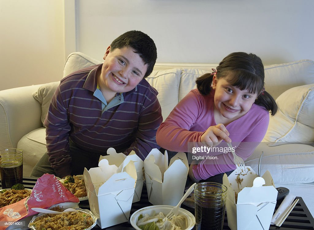 Overweight Brother and Sister Sitting Side by Side on a Sofa Eating Takeaway Food : Stock Photo