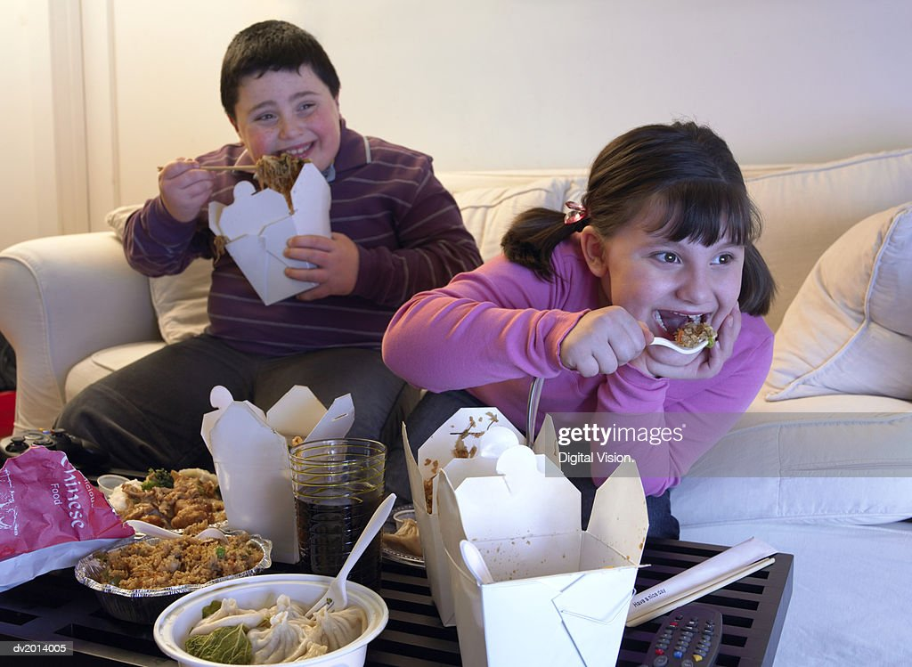 Overweight Brother and Sister Sitting Side by Side on a Sofa Eating Takeaway Food and Watching the TV : Stock Photo