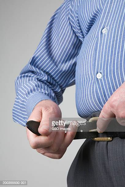 Overweight businessman fastening belt, mid section, close-up