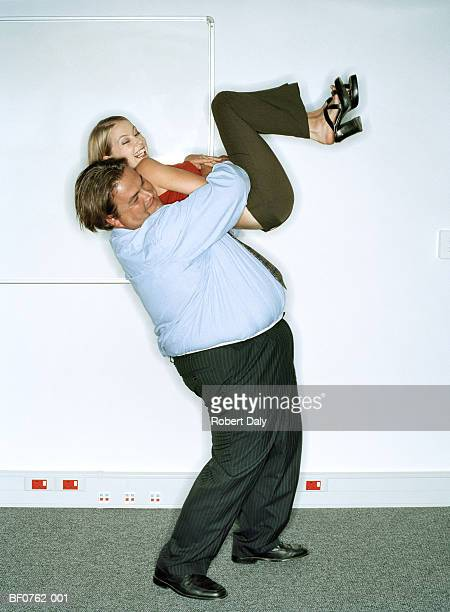 overweight businessman lifting petit woman in the air, laughing - skinny man fat woman stock pictures, royalty-free photos & images