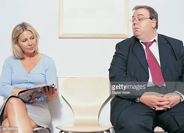 Overweight Businessman Looking at Woman's Magazine In Doctor's Office