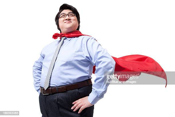 Overweight businessman playing the part of superman