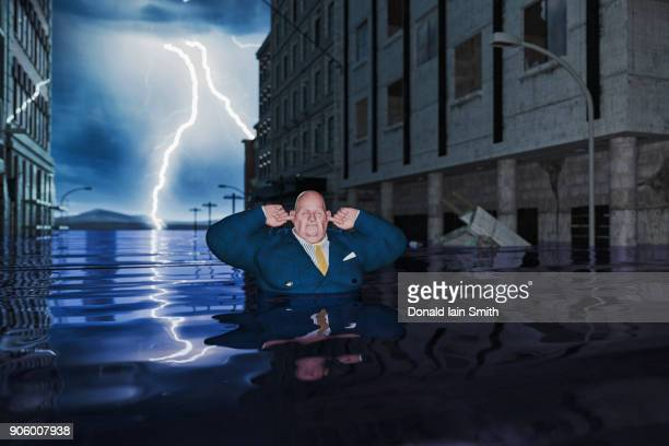 overweight businessman with fingers in ears in flooded city - greedy smith stock pictures, royalty-free photos & images