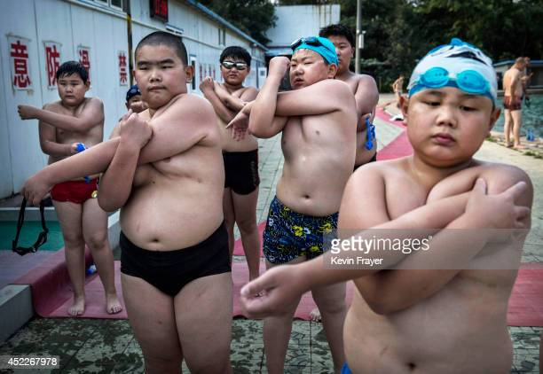Overweight Chinese students stretch after swimming during training at a camp held for overweight children on July 15 2014 in Beijing China Obesity is...