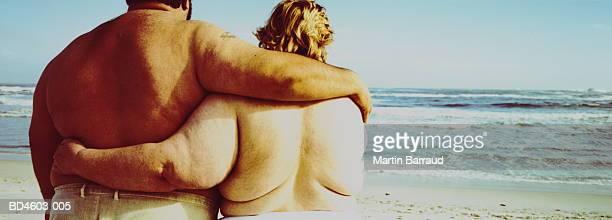 overweight couple embracing on beach, rear view - dicke frauen am strand stock-fotos und bilder