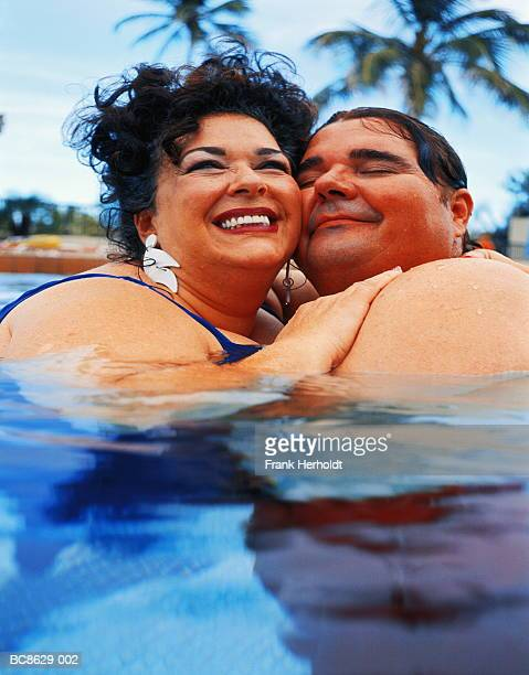 overweight couple in swimming pool, embracing, close-up - funny fat women stock pictures, royalty-free photos & images