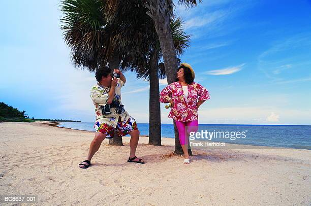 Overweight couple on beach, man taking photograph of woman