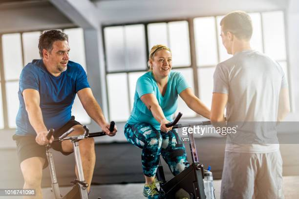 Overweight couple on exercise bikes talking with personal trainer
