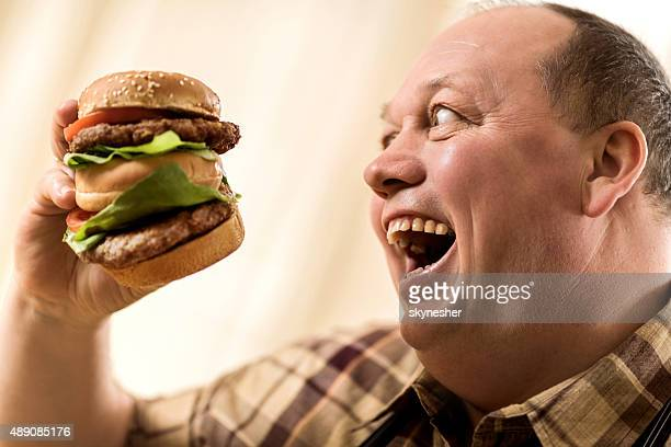 overweight excited man about to eat a huge hamburger. - over eating stock pictures, royalty-free photos & images