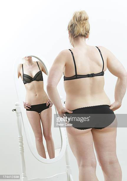 overweight girl looking at underweight reflection - fat blonde women stock photos and pictures