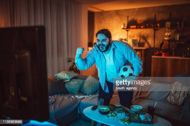 homme en surpoids regardant un match de football à la maison - homme gros ventre photos et images de collection
