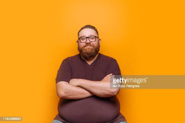 overweight hipster on yellow background - sfondo a colori foto e immagini stock