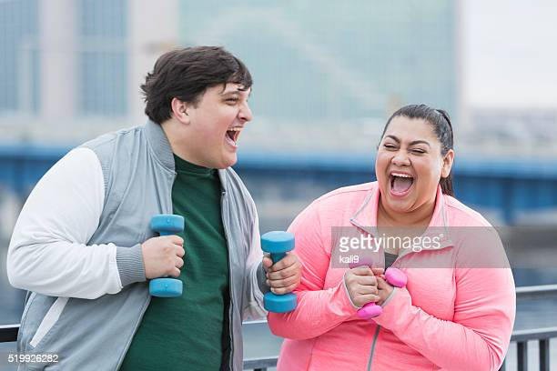 Overweight Hispanic man and woman exercising, laughing
