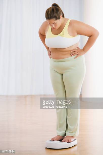Overweight Hispanic woman on scale