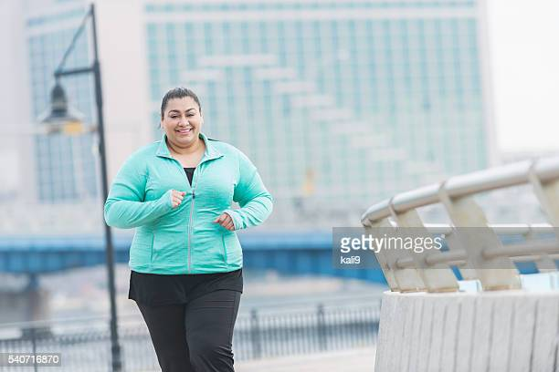 Overweight Hispanic woman running or jogging outdoors