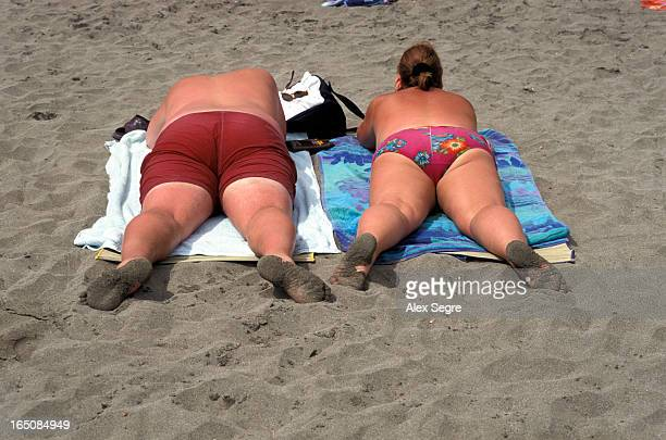 CONTENT] Overweight holidaymakers sunbathing on beach in Tenerife Canary Islands Spain