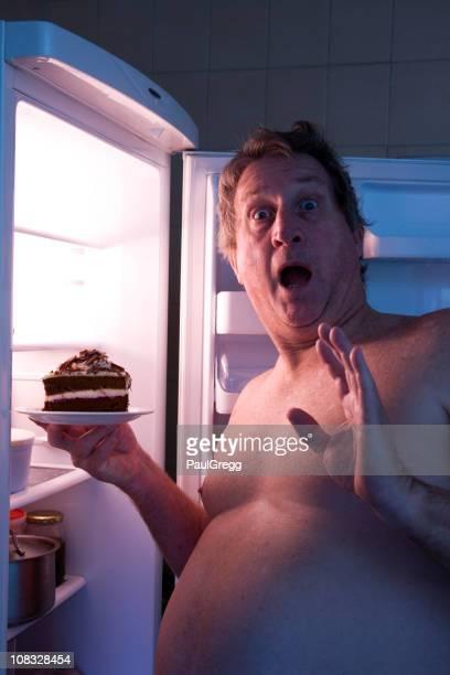 Übergewichtige männliche Gefangene in den Kühlschrank, die auf der Suche nach Essen.